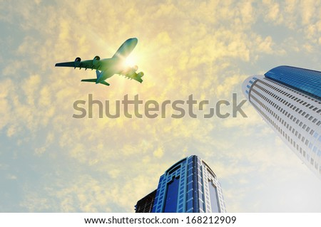 Image of airplane flying above skyscrapers. Bottom view - stock photo