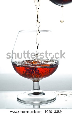 Image of alcohol drink pouring into glass - stock photo