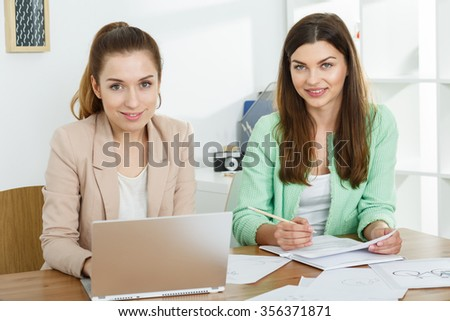 Image of ambitious female co-workers creating business project