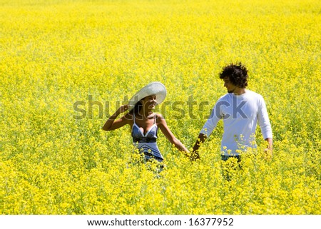 Image of amorous couple walking in yellow meadow holding by hands and looking at each other - stock photo
