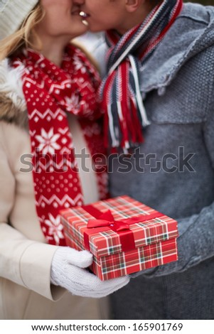Image of amorous guy giving his girlfriend Christmas present while kissing her - stock photo