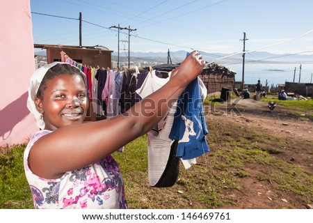 image of an african woman hanging her clean laundry in the sunny outdoors with a proud smirk on her face