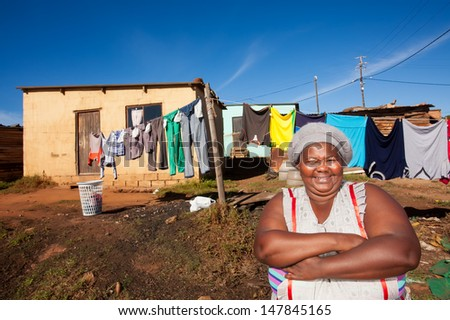 image of an african woman standing proudly with her arms crossed in front of her home with laundry on the washing line - stock photo