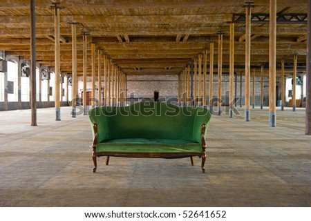 Image of an antique green couch in old, loft style building with wooden columns