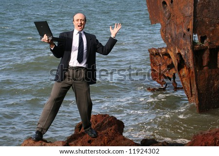 Image of an assessor or business man in trouble on the rocks in front of a ship wreck. - stock photo