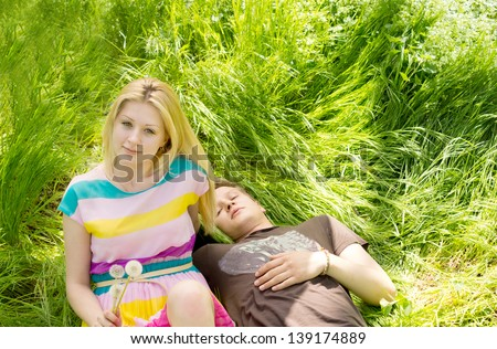 Image of an attractive couple lying down on the grass, having fun on a romantic picnic date - stock photo