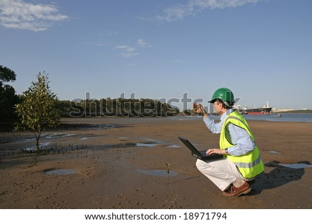Image of an ecologist taking samples next to a river - stock photo
