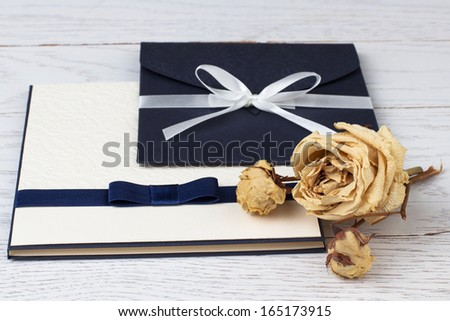 Image of an elegant envelope and an album on the table. - stock photo