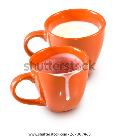 image of an empty cup and a cup of milk - stock photo