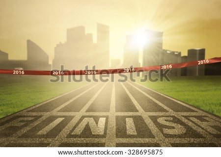 Image of an empty finish line with numbers 2016 on the tape and bright sun rays at the end of track