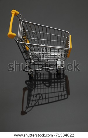 Image of an empty shopping cart and its shadows against a black background. - stock photo