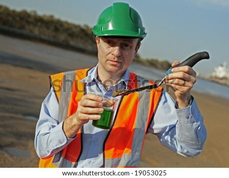 Image of an environmental officer in the field testing samples beside a city river. - stock photo