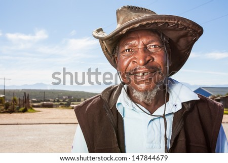 image of an old african man wearing a leather farming hat standing outside smiling with watery eyes - stock photo