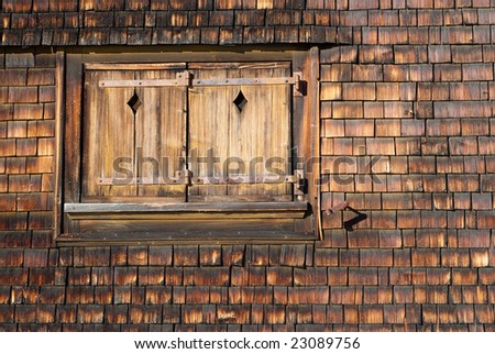 image of an old closed window on a stained wooden facade