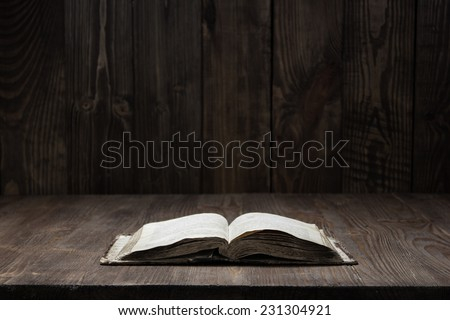 Image of an old Holy Bible on wooden background in a dark space - stock photo