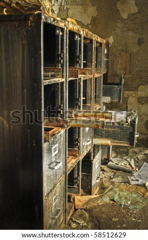 Image of an old rusty filing cabinet in a derelict abandoned police station covered in debris. - stock photo