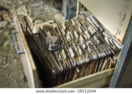 Image of an old rusty filing cabinet in a derelict abandoned police station covered in dust and debris. - stock photo