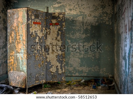 Image of an old rusty locker in a derelict abandoned building near a crumbling wall with peeling paint. - stock photo