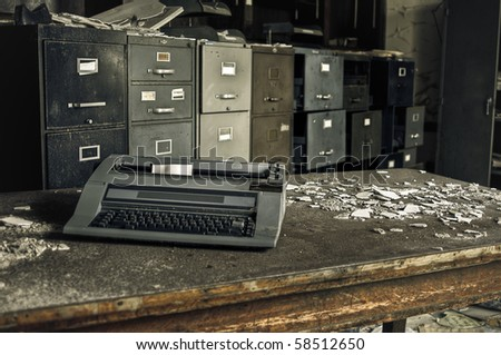 Image of an old rusty typewriter in a derelict abandoned building with old filing cabinets in the background.