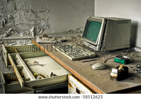 Image of an old, vintage computer in a derelict abandoned police station covered in debris and dust. - stock photo