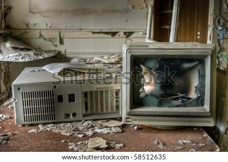Image of an old, vintage destroyed computer in a derelict abandoned police station covered in debris and dust. - stock photo