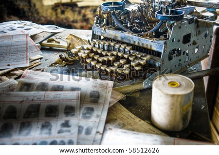 Image of an old, vintage rusty typewriter in a derelict abandoned police station with criminal fingerprint files scattered on the desk. - stock photo