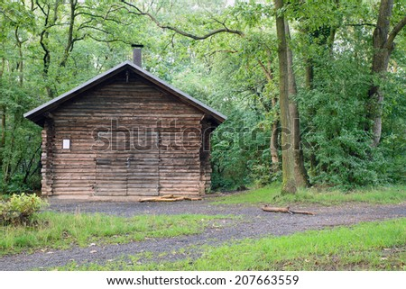 Image of an old wooden log cabin in the middle of a forest - stock photo