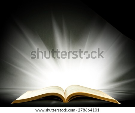 image of an open book with a beautiful light on a black background