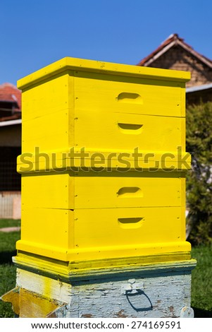 Image of an yellow wooden freshly painted beehive in a courtyard. - stock photo