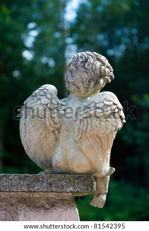 Image of an / young and sad Angel / sitting on a pillar in front of a forest - stock photo