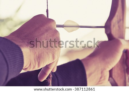 image of Archer holds his bow aiming at a target  - stock photo