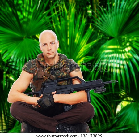 Image of armed soldier who is sitting in jungles - stock photo