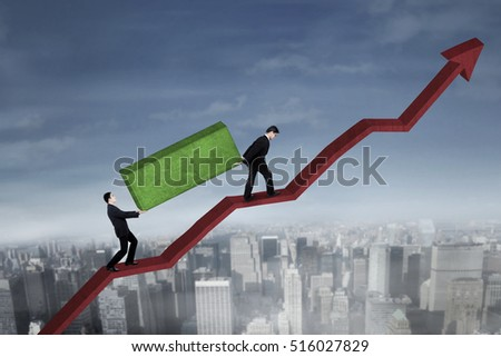 Image of Asian business people lifting boulder together while walking on the upward red arrow