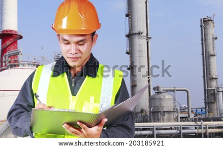 Image of asian engineer with oil gas industry in the background