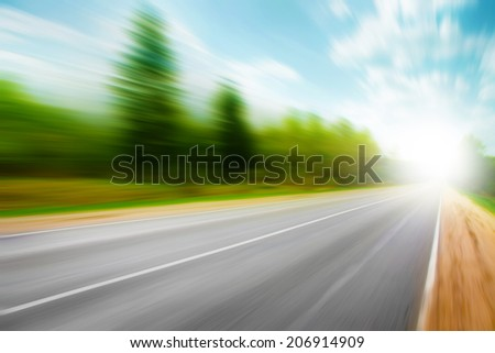 Image of asphalt road in motion blur on summer day.   - stock photo