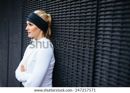 Image of attractive and sporty young woman standing against a wall looking away. Taking a break from outdoor training session. - stock photo