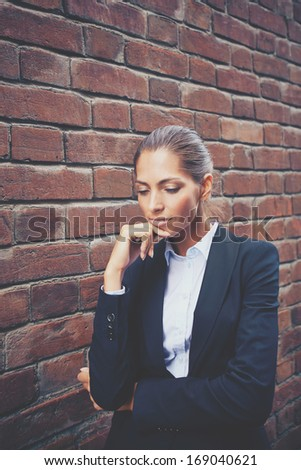 Image of attractive businesswoman in suit with pensive expression   - stock photo