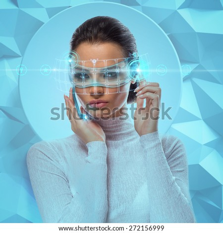 Image of Attractive Businesswoman Wearing Futuristic virtual Glasses Working With Holographic Hud Against Hightech background - stock photo