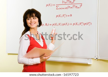 Image of attractive teacher writing formula on whiteboard during lesson - stock photo