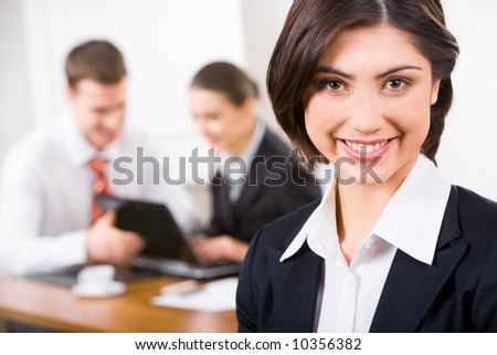 Image of attractive woman with charming smile on the background of business people
