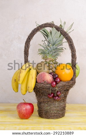 Image of basket with fruits on yellow wooden table, vertical. - stock photo