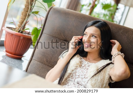 image of beautiful brunette woman sexy girl having fun sitting in a restaurant lounge or coffee shop and talking on mobile cell phone happy smiling touching her hair & looking at copy space window - stock photo