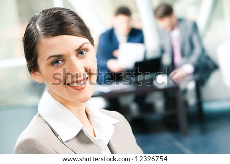 Image of beautiful business woman looking at camera in a working environment - stock photo