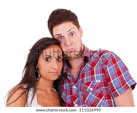 Image of beautiful fashion couple shot in studio - the boy has a goofy look on his face while she stays serious - stock photo