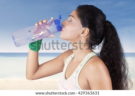 Image of beautiful indian woman wearing sportswear and drinking water with a bottle after workout at beach - stock photo