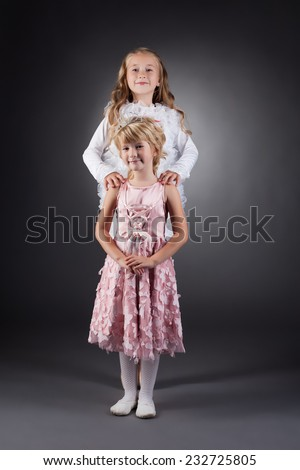 Image of beautiful little sisters posing in studio - stock photo