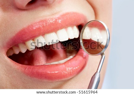 Image of beautiful mouth with health teeth and mirror