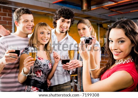 Image of beautiful smiling woman holding the camera at the evening-party - stock photo