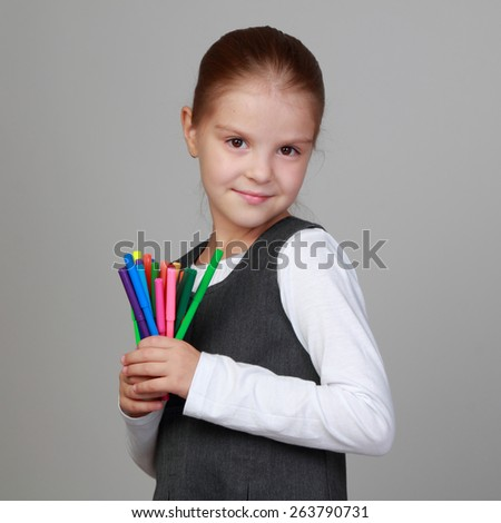 Image of beautiful sweet little schoolgirl holding felt tip pens on Education