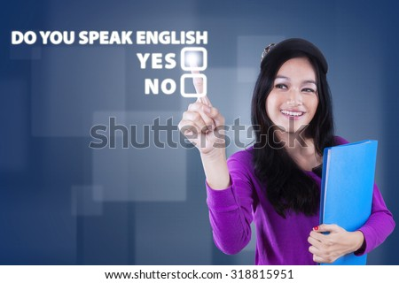 Image of beautiful teenage girl learn english speaking and touching a text of Do You Speak English? - stock photo